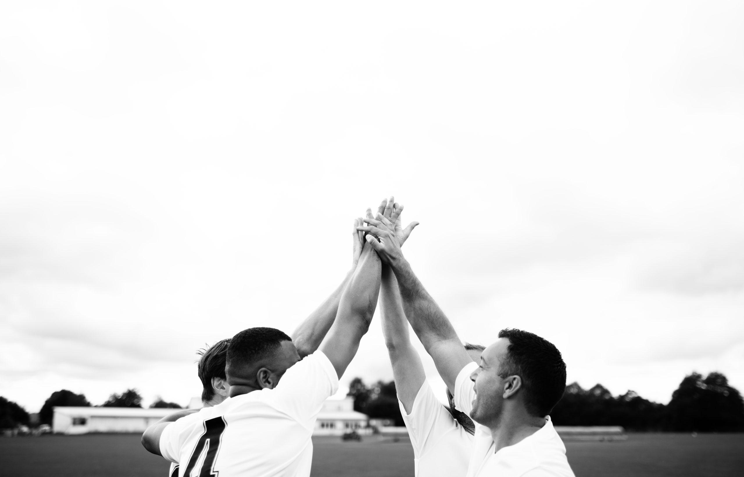 Image en noir et blanc de 4 joueurs de rugby les mains réunies lors d'un hi 5 - Chaudronnerie Marmonier partenaire du rugby