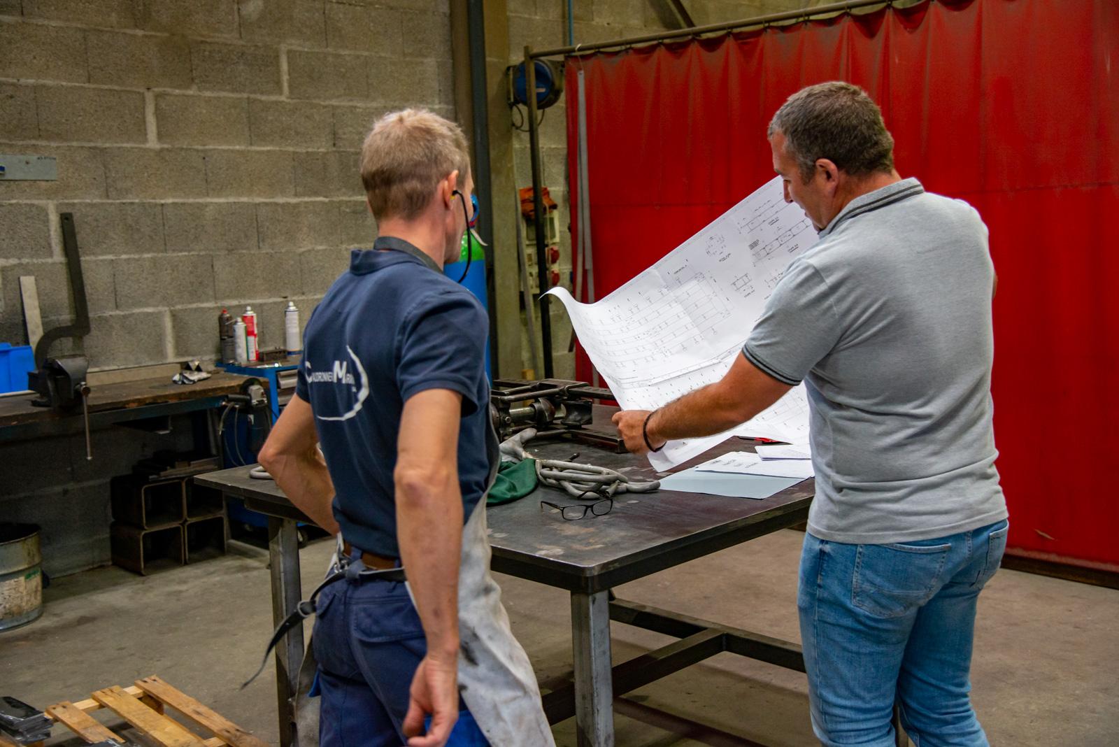 2 employés de la chaudronnerie Marmonier regardant le plan de construction d'un four en inox
