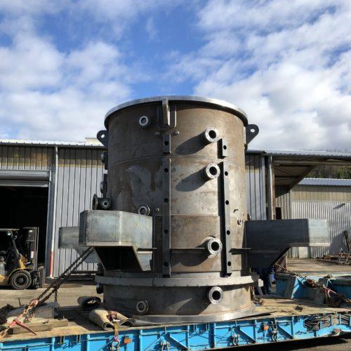 Photo d'un four sous vide en acier devant un hangar de la chaudronnerie Marmonier, fabriquant de fours industriels en Rhône-Alpes