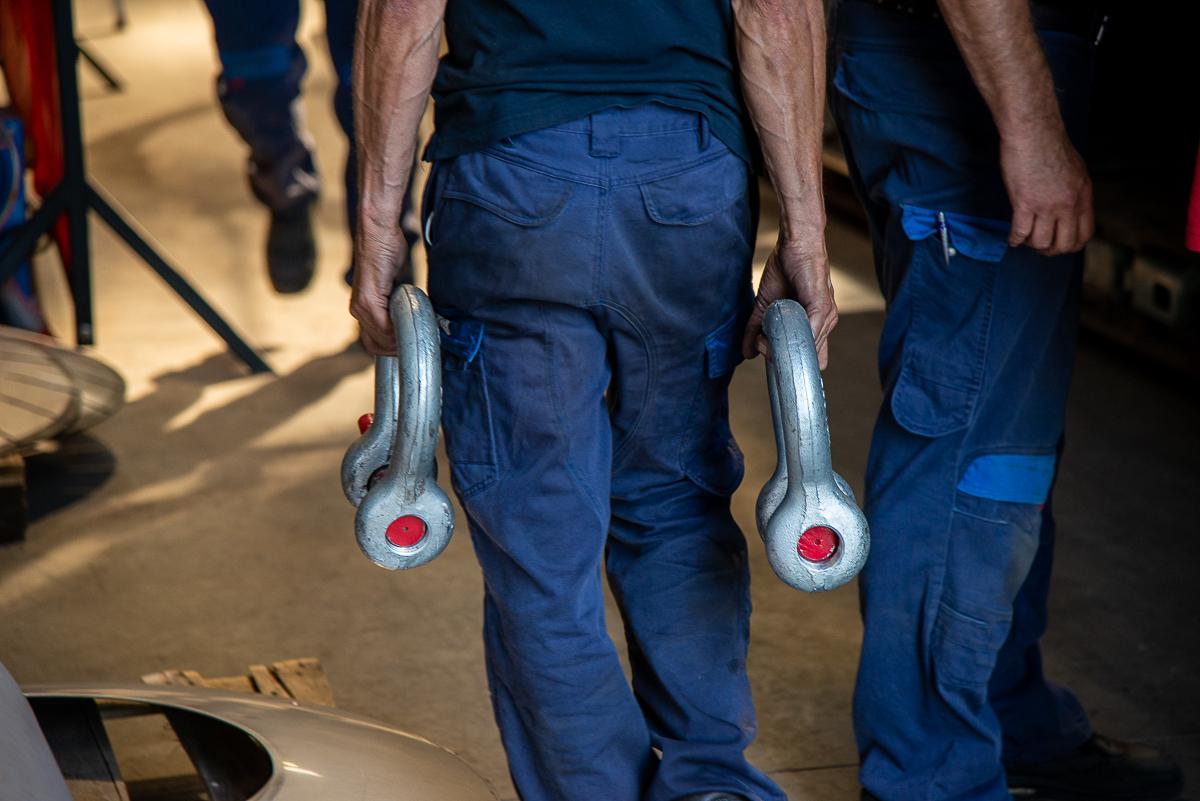 Ouvrier de dos qui tient une manille de levage dans chacune de ses mains - Chaudronnerie Marmonier - le savoir-faire industriel