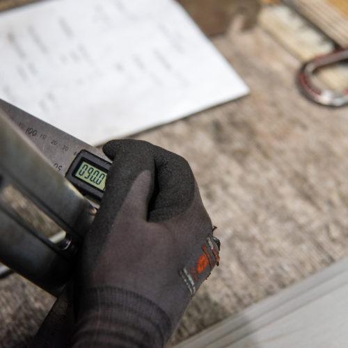 Main qui tient un rapporteur d'angles numérique destiné aux calculs et à la fabrication de pièces industrielles - Marmonier